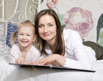 Porträt der glücklichen Familie, der Mutter und der Tochter im Bettlesebuch Lizenzfreie Stockbilder