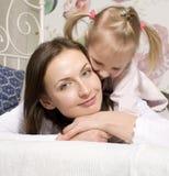 Porträt der glücklichen Familie, der Mutter und der Tochter im Bettlesebuch Lizenzfreie Stockfotografie