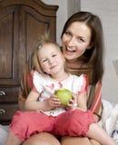 Porträt der glücklichen Familie, der Mutter und der Tochter im Bettlesebuch Lizenzfreie Stockfotos