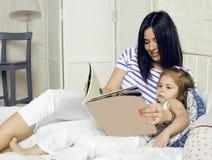 Porträt der glücklichen Familie, der Mutter und der Tochter im Bettlesebuch Stockbild