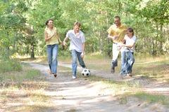Porträt der glücklichen Familie Fußball im Park spielend lizenzfreie stockfotos