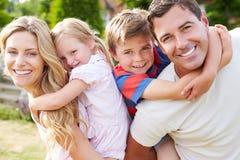 Porträt der glücklichen Familie im Garten Stockfotografie