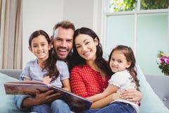 Porträt der glücklichen Familie mit Bilderbuch auf Sofa Stockfotografie