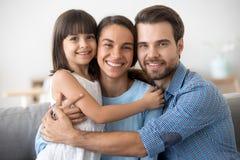 Portr?t der gl?cklichen Familie mit dem Kind, welches die Aufstellung f?r Bild umarmt lizenzfreies stockbild