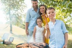 Porträt der glücklichen Familie mit zwei Kindern, die draußen nahe Grill stehen Stockbilder