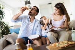 Porträt der glücklichen Familie Pizza zu Hause teilend lizenzfreie stockfotos