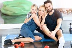Porträt der glücklichen Familie sitzend auf Matte stockfotografie