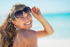 Porträt der glücklichen Frau in der Sonnenbrille auf Strand Stockbild