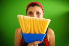 Porträt der glücklichen Frau die Aufgaben tuend, die Besen halten Stockbilder