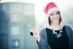 Porträt der glücklichen Frau, die Bengal-Lichter über Stadthintergrund hält Weihnachtsfrau mit Sparkler Porträt des lächelnden br Lizenzfreie Stockfotografie