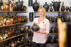 Porträt der glücklichen Frau keramisches Gerät wählend Stockfotografie