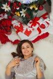 Porträt der glücklichen Frau legend nahe Weihnachtsbaum Stockfotografie