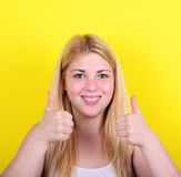 Porträt der glücklichen Frau mit den Daumen oben gegen gelben Hintergrund Lizenzfreie Stockfotografie