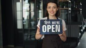 Porträt der glücklichen Geschäftsfrau im Schutzblech, das offene Zeichenstellung im neuen Café hält stock video
