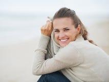 Porträt der glücklichen jungen Frau in der Strickjacke, die auf einsamem Strand sitzt Stockbilder