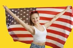 Porträt der glücklichen jungen Frau, die amerikanische Flagge über gelbem Hintergrund hält Lizenzfreies Stockbild