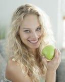 Porträt der glücklichen jungen Frau, die Apfel im Haus hält Stockfoto