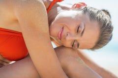 Porträt der glücklichen jungen Frau, die auf Strand sich entspannt Stockbilder