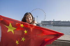 Porträt der glücklichen jungen Frau, die chinesische Flagge gegen London-Auge in London, England, Großbritannien hält Lizenzfreies Stockfoto