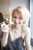 Porträt der glücklichen jungen Frau, die Gebäck im Café isst Stockbild