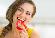 Porträt der glücklichen jungen Frau, die grünen Pfeffer isst lizenzfreies stockbild