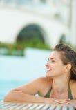 Porträt der glücklichen jungen Frau, die im Pool sich entspannt Stockbilder