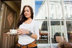 Porträt der glücklichen jungen Frau, die Kaffeetasse vor Café hält Stockbild