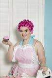 Porträt der glücklichen jungen Frau, die kleinen Kuchen beim Bügeln hält Lizenzfreie Stockfotos