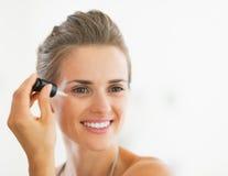 Porträt der glücklichen jungen Frau, die kosmetisches Serum anwendet Stockbild