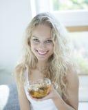 Porträt der glücklichen jungen Frau, die Kräuterteeschale im Haus hält Stockbilder
