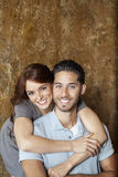 Porträt der glücklichen jungen Frau, die Mann von hinten umarmt Lizenzfreie Stockfotos