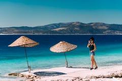 Porträt der glücklichen jungen Frau, die in Meer lächelt Reisenkoffer mit Meerblick nach innen Schöner junger Brunette auf einem  lizenzfreies stockfoto