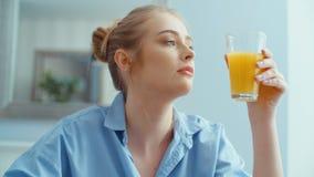 Porträt der glücklichen jungen Frau, die Orangensaft während des Frühstücks trinkt stock video footage