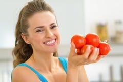 Porträt der glücklichen jungen Frau, die Tomate zeigt Stockbild