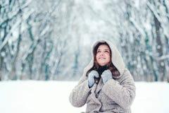 Porträt der glücklichen jungen Frau an einem schneienden Wintertag, in einem Park Stockfoto