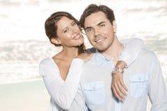 Porträt der glücklichen jungen Frau mit dem Arm um Mann am Strand Lizenzfreie Stockfotografie