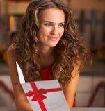 Porträt der glücklichen jungen Frau mit Weihnachtspostkarte in der Küche Stockfotos