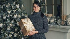 Porträt der glücklichen jungen Frau in der modischen Strickjackenholding-Geschenkboxstellung nahe verziertem dem Weihnachtsbaum u stock footage