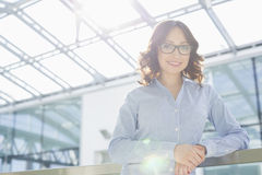 Porträt der glücklichen jungen Geschäftsfrau, die auf Geländer im Büro sich lehnt Stockfotos