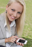 Porträt der glücklichen jungen Geschäftsfrau, die intelligentes Telefon im Rasen verwendet Stockbild