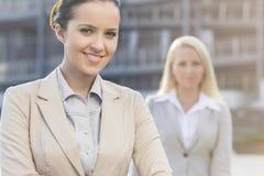 Porträt der glücklichen jungen Geschäftsfrau mit weiblichem Kollegen im Hintergrund Stockfoto
