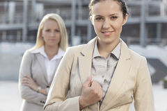 Porträt der glücklichen jungen Geschäftsfrau mit weiblichem Kollegen im Hintergrund Lizenzfreie Stockbilder