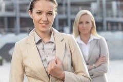 Porträt der glücklichen jungen Geschäftsfrau mit weiblichem Kollegen im Hintergrund Stockfotografie