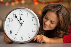 Porträt der glücklichen jungen Hausfrau, die auf Uhr schaut Lizenzfreie Stockfotografie