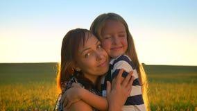 Porträt der glücklichen jungen Mutter, die kleine blonde Tochter, Kamera und herein lächeln, Weizen- oder Roggenfeld betrachtend  stock video footage