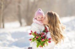 Porträt der glücklichen jungen Mutter küsst ihr Baby am sonnigen Tag des Winters lizenzfreie stockfotos