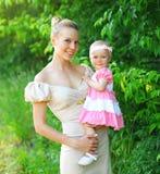 Porträt der glücklichen jungen Mutter- und Babytochter, die ein Kleid trägt Stockfotografie