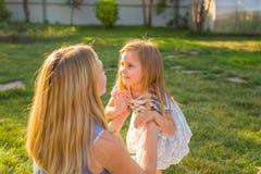 Porträt der glücklichen liebevollen Mutter und ihrer der Babytochter, die draußen spielt lizenzfreie stockfotos