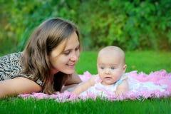 Porträt der glücklichen liebevollen Mutter und ihres Babys draußen Stockbild