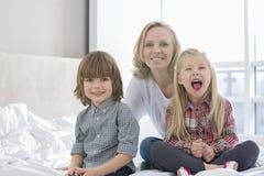 Porträt der glücklichen Mutter mit Kindern im Schlafzimmer Stockfoto